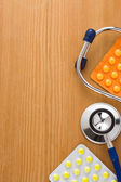 Stethoscope with pills on wood — Stock Photo