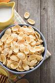 Bowl of corn flakes on wood — Stock Photo