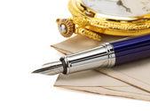 Klocka och penna på kuvert — Stockfoto