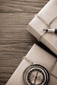 Parcel wrapped with brown paper on wood — Stock Photo