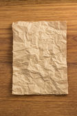 Wrinkled paper  on wood — 图库照片