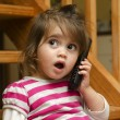 Little girl speak on the phone - Stock Photo