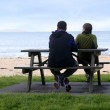 Young couple seat on opposite sides of park bench. — Stock Photo #13051259