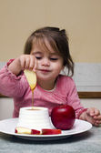 Little Jewish girl dipping apple slices into honey — Stock Photo