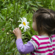 Royalty-Free Stock Photo: Girl smells daisy flower