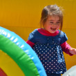 Stock Photo: Little girl play in inflatable jumper playground