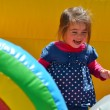 Little girl play in inflatable jumper playground - Foto Stock