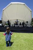 Little girl dances in a music concert — Stock Photo