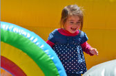 Little girl play in inflatable jumper playground — Stock Photo