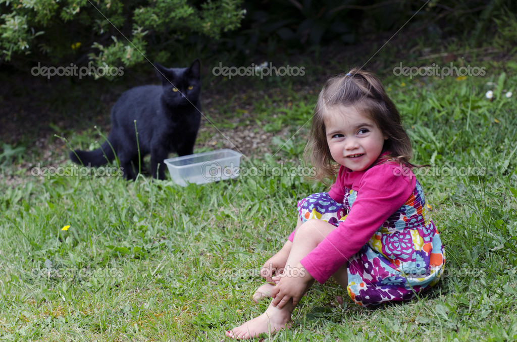 Little girl plays with a black cat in the garden. — Stock Photo #14436105