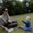 Mother and her little girl playing with soap bubbles — Stock Photo
