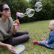 Mother and her little girl playing with soap bubbles — Stock Photo #14938683
