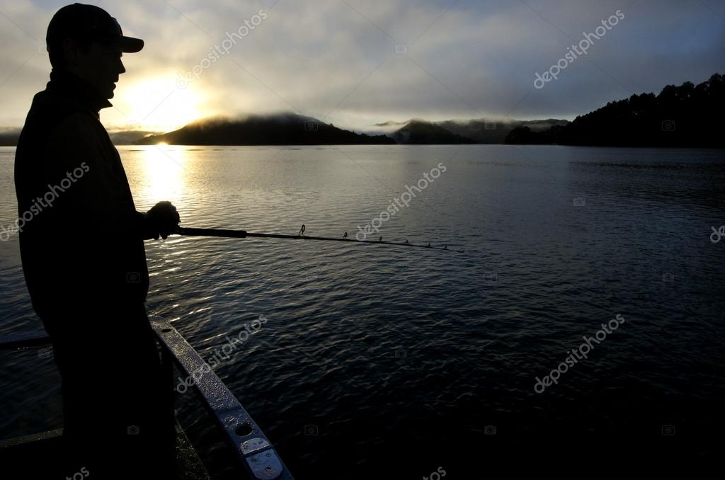Fisherman holds a fishing rod during sunrise and sunset. — Stock Photo #14939231
