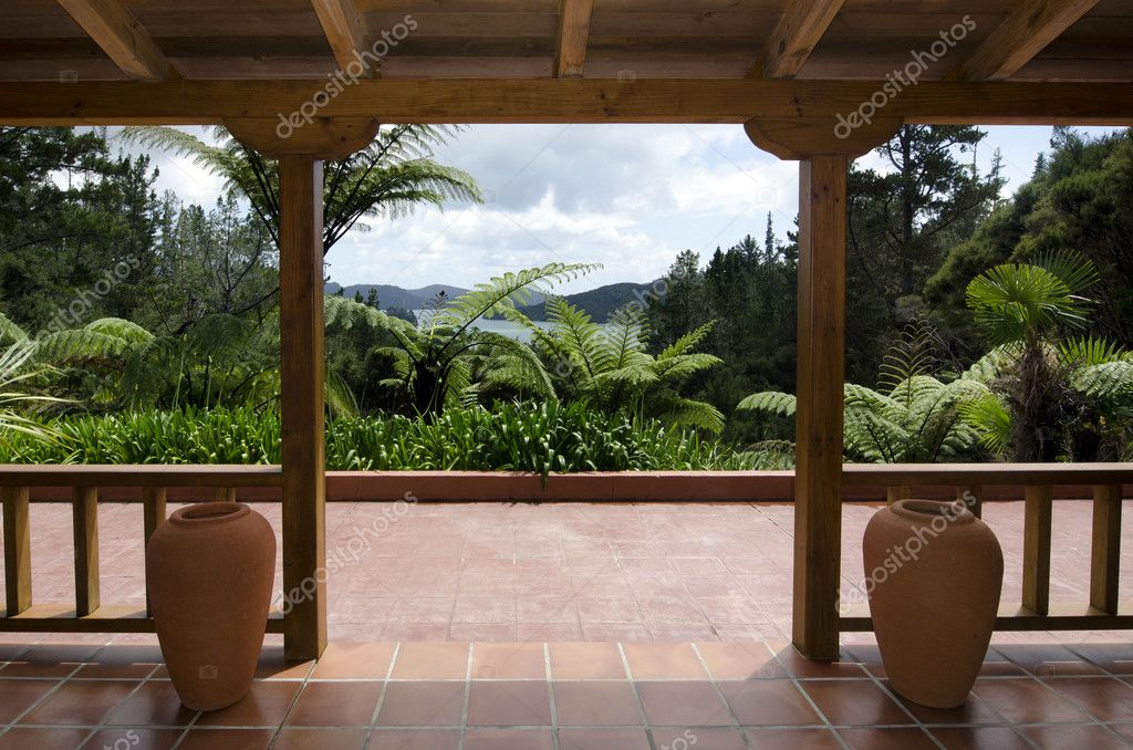 A sub tropical wooden patio near bush and grass. — Stock Photo #14940053