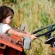 Small child sitting on an old tractor  — Stock Photo