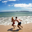Couple play on empty beach in New Zealand — Stock fotografie