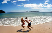 Couple play on empty beach in New Zealand — Stock Photo