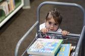 Preschool girl in library — Stock Photo