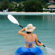 Young caucasian woman kayaking over turquoise water — Stock Photo