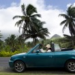 Постер, плакат: Young woman traveling by convertible car in a Pacific Island