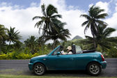 Young woman traveling by convertible car in a Pacific Island — Stock Photo