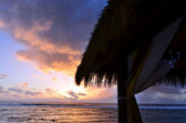 Tropical sunset over a beach bungalow — ストック写真