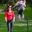 Young mother swing a child in playground — Stock Photo