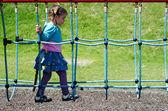 Barnet passerar över hängbro på lekplats — Stockfoto