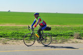 Cyclist riding a bike on an open road — Stock Photo