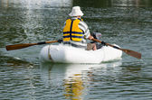 Man rows dinghy boat — Stock Photo