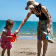Mother and child plays on the beach — Stock Photo