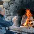Stock Photo: Mature man warm up with fireplace