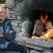 Mature man warm up with fireplace — Stock Photo #40569653