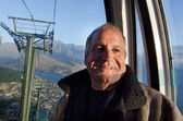 Mature man travel by aerial tramway — Stock Photo
