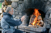 Mature man warm up with fireplace — 图库照片