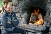 Mature man warm up with fireplace — Stock fotografie