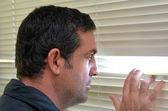 Man looking through blinds — Stock Photo