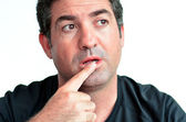 Mature man thinking with one finger on his lips  — Stock Photo