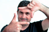 Serious mature man creating frame with fingers — Stock Photo