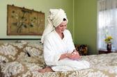 Young woman applies moisturiser to her skin — Stock Photo