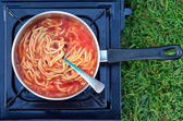 Caned spaghetti cooked outdoors — Stock Photo