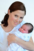 Mother and newborn baby kissing and hugging. — Stock Photo