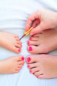 Mother and child paint their feet with nail polish — Stock Photo