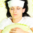 Stock Photo: Young woman with eyes closed being ill in bed