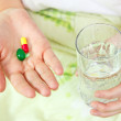 Woman holding two pills and a glass of water. — Stock Photo #13557612
