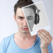 Stock Photo: Young male holding photo with himself with headphones