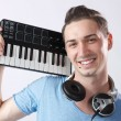 Deejay with headphones and midi keyboard on shoulder — Stock Photo
