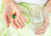 Femme tenant deux pilules et un verre d'eau. — Photo