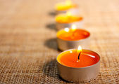 Four burning orange candles placed on jute material — Stock fotografie