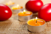Closeup of rounded candles placed between three red egg — Стоковое фото